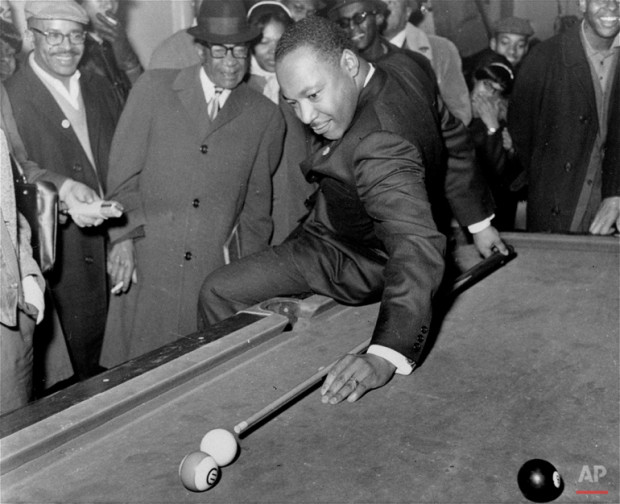 During a visit to a pool hall, February 18, 1966, Dr. Martin Luther King, Jr., campaigning in Chicago, IL. for better living conditions for African Americans, demonstrates some proficiency with a cue. (AP Photo)